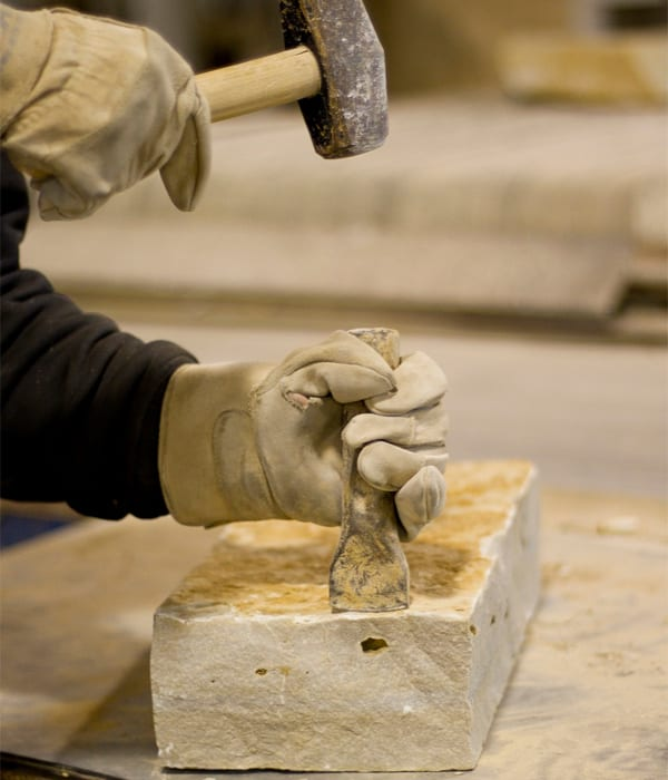 Hammering and chisel on piece of natural stone